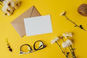 blanco kaart met envelop, bril en bloem wordt op geel geplaatst foto