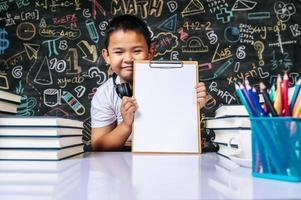 kind zit en toont klembord in de klas foto