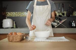 vrouwelijke kok in een witte schort kraakt een ei in de keuken van het huis. foto