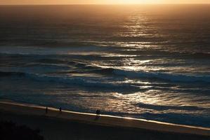 vroege zonsopgang op het oceaanstrand, zeegezicht, silhouetten mensen foto