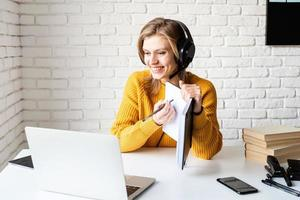 jonge vrouw in zwarte koptelefoon die online studeert met behulp van laptop foto