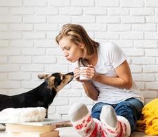 vrouw zittend op de vloer met haar honden koffie drinkend foto