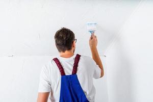 man in blauwe overall schilderen muur met roller foto