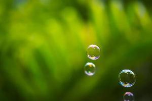 waterbellen drijven en vallen op groene bladeren foto
