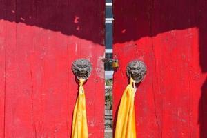 rode houten deur met metalen deurring arou da tempel in qinghai china. foto