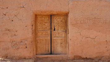 oude huis muur houten deur in tuyoq dorpsvallei xinjiang china. foto