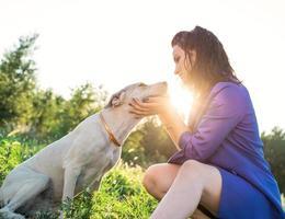 jonge aantrekkelijke vrouw haar hond knuffelen in het park in de zonsondergang foto