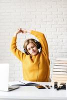 vrouw zit aan het bureau die zich uitstrekt na lange studie foto