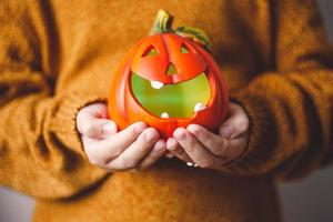 Halloween-pompoenlamp in de handen van kinderen. foto