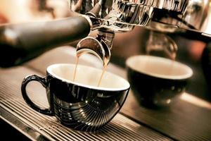 espresso shot uit koffiezetapparaat in coffeeshop foto