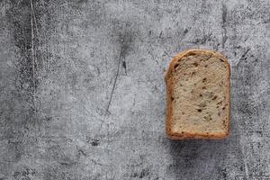 gesneden graan volkoren brood op donkere rustieke houten achtergrond foto