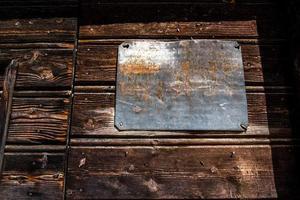 lege ijzeren plaquette op houten deur in san martino di castrozza, trento, italië foto