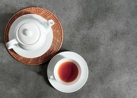 witte porseleinen theekop en theepot, afternoon tea-tafelsetting foto
