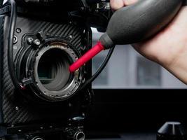 met behulp van een rubberen inflator om het sensorglas van de filmcamera schoon te maken. foto