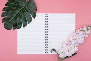wit dagboekboek met bloemen en groen blad op roze achtergrond foto