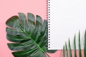 wit dagboekboek met groene bladeren op roze achtergrond foto