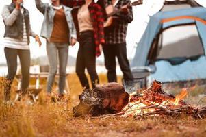 close-up van kampvuur en vriendschap dansen op het ritme van de muziek foto