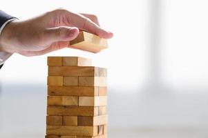 zakenman die houtblok schikt en met de hand als toren stapelt foto
