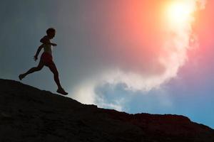 vrouw rent op de bergkam met kleurrijke zon foto
