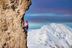 een jong meisje bergbeklimmer tijdens een klim foto