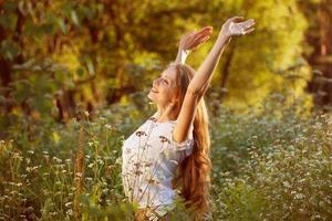 gelukkige jonge vrouw tussen de wilde bloemen foto