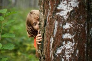 jongen die vanachter een boomstam naar buiten gluurt foto
