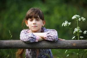 mooi klein meisje tussen de wilde bloemen foto