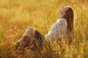 gelukkige vrouw die in het gras zit foto