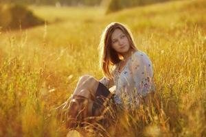 mooie vrouw zittend in een weiland foto