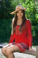 mooi meisje in een rode jurk en een hoed foto