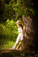 meisje staat in de buurt van een boom in het zonlicht foto