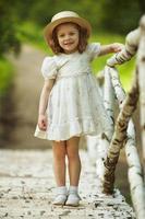 klein meisje in een jurk en hoed foto