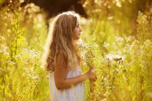 schattig klein meisje tussen witte wilde bloemen foto