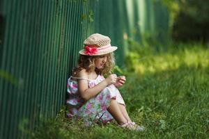 meisje zit tegen een hek geleund foto
