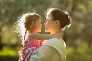 gelukkige moeder die zijn dochtertje vasthoudt foto