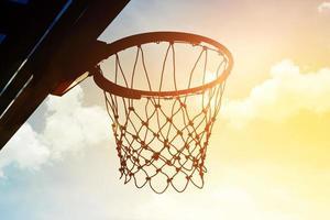 basketbalring buiten in de wolken en de lucht zonsondergang foto