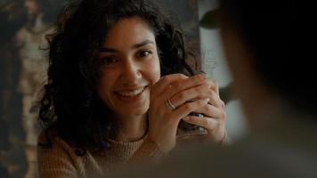 vrouw zit en drinkt koffie terwijl ze met de man aan tafel praat foto