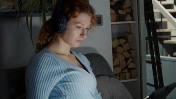 jonge blanke vrouw in woonkamer, koptelefoon op oren kijken naar tablet foto