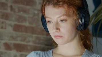 jonge blanke vrouw zitten met koptelefoon, kijken naar tablet op schoot foto