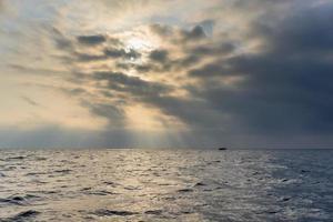 de zee bij bewolkt en mistig weer met drijvende boot foto