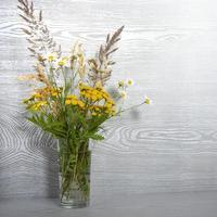 een boeket wilde bloemen in een glazen vaas op een houten tafel foto