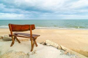 houten bank op strand met zee strand achtergrond foto