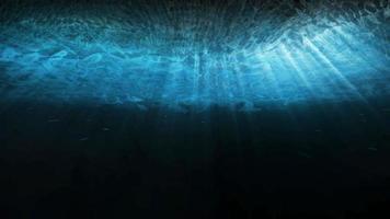 diepblauw onderwater met zonlichtstralen die door het oceaanoppervlak schijnen foto