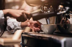 close-up van professionele vrouwelijke barista-hand die een kopje koffie maakt foto