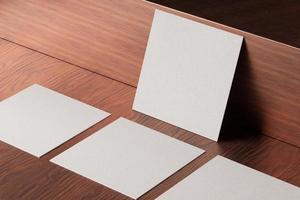 witte vierkante papieren visitekaartje mockup op houten bruine tafel foto