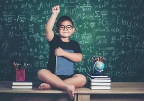 jongen met boeken zitten in de buurt van groen schoolbord foto