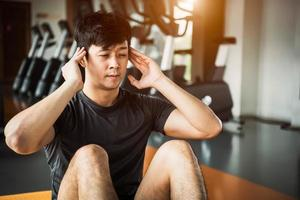 Aziatische sportman doet crunch of zit rechtop op yogamat foto