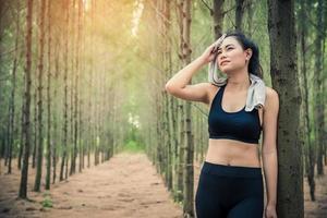 Aziatische schoonheidsvrouw die het zweet in bos afveegt foto