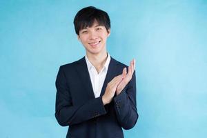 afbeelding van een jonge Aziatische zakenman die een pak draagt op een blauwe achtergrond foto