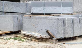 gefacetteerde granieten stoepranden op een pallet. gladde porseleinen steengoedproducten foto